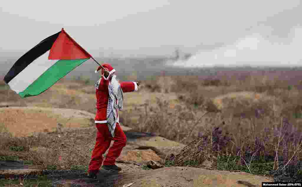 A Palestinian protester dressed as Santa Claus waves a Palestinian flag during clashes following protests against U.S. President Trump's decision to recognize Jerusalem as the capital of Israel. (epa-EFE/Mohammed Saber)