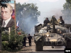 Российские танки проезжают мимо портрета тогдашнего премьер-министра Владимира Путина в городе Цхинвали в Южной Осетии. 20 августа 2008 года.