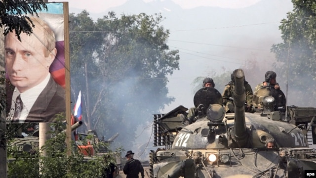 A Russian tank passes by a huge portrait of Vladimir Putin. (file photo)