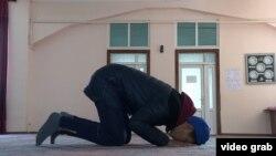 Молодой парень молится в спортзале внутри мечети в Бишкеке.