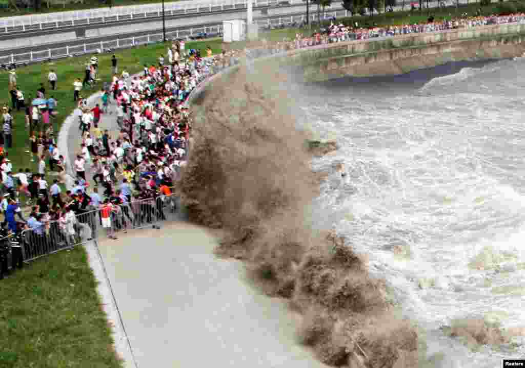 People run away from waves as they watch the tidal bore in Hangzhou, Zhejiang Province, China. (Reuters)