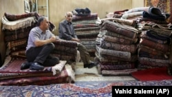 In this Aug. 10, 2015 file photo, Iranian merchants wait for customers at a carpet shop in Tehran's old, main bazaar, Iran.