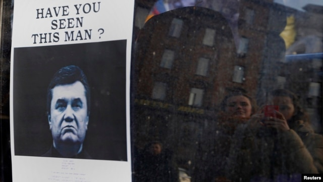 "People look at a ""Wanted"" notice for fugitive President Victor Yanukovych, plastered on the window of a car used as barricade near Kyiv's Independence Square on February 24."