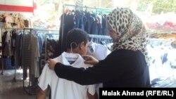 أم عراقية تقيس على إبنها ملابس للعام الدراسي الجديد