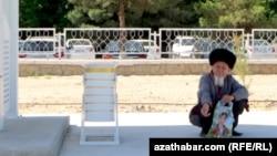 Türkmənistan. Qoca kişi dayanacaqda kölgədə oturub.