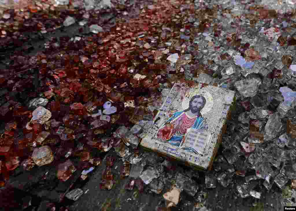 A bloodstained icon of Jesus is seen among shattered glass atop a wrecked KamAZ truck near the Donetsk airport in eastern Ukraine following a gunbattle on May 26-27. (Reuters/Yannis Behrakis)