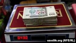 Пачка узбекских сумов на весах. Сумма в пачке эквивалента 100 долларам США.