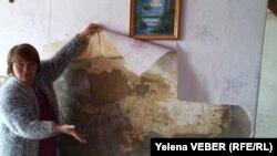 Жительница села Чкалово Карагандинской области показывает поврежденную стену дома после паводков. 28 апреля 2017 года.