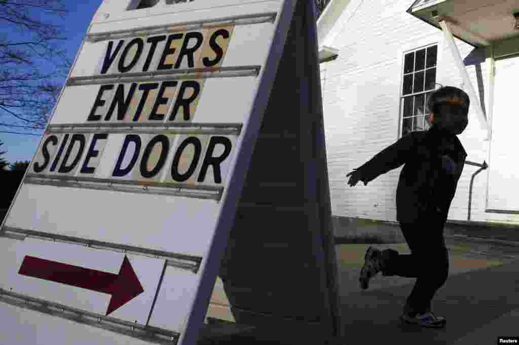 A boy runs to tell voters where to enter the Town Hall of Canterbury, New Hampshire.