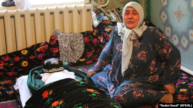 A relative mourns over the body of 27-year-old Hamza Ikromzoda, who died in Tajik detention. Family members say the body showed signs of torture.