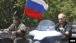 Russian Prime Minister Vladimir Putin (right) rides a Harley Davidson Lehman Trike as he arrives for a meeting with Russian and Ukrainian motorbikers at their camp near Sevastopol on July 24.