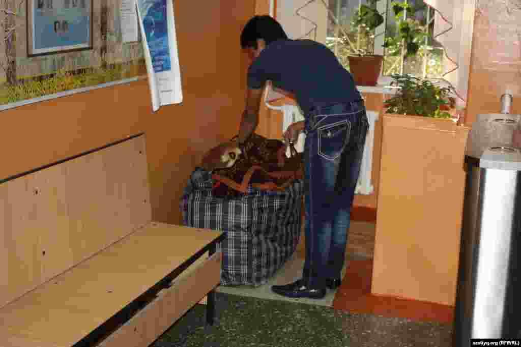 Первокурсник Айтбек распаковывает свои вещи в обжещитии.