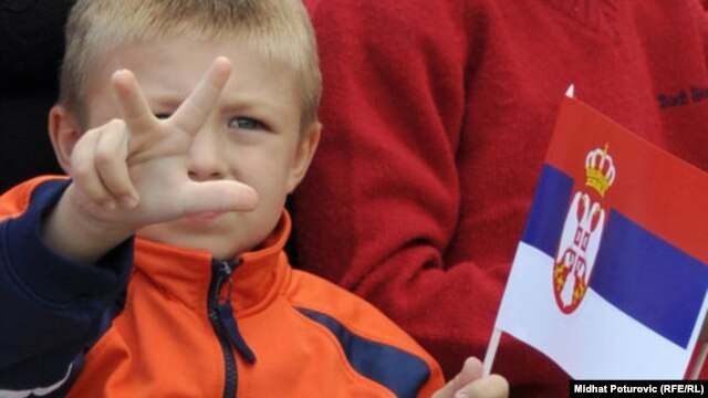 A child shows the traditional Serb three-finger salute in Pale, in Bosnia's Republika Srpska, on September 8. He's waving the Serbian flag.