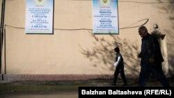 Сайлауға қатысуға шақыратын плакаттың жанынан өтіп бара жатқан адамдар. Алматы, 20 наурыз 2016 жыл.