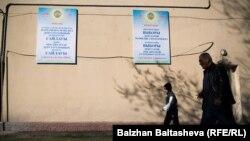 Люди проходят мимо плакатов, призывающих голосовать на выборах. Алматы, 20 марта 2016 года.