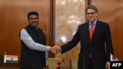 Indian Minister for Petroleum and Natural Gas Dharmendra Pradhan (L) shakes hand with US Energy Secretary Rick Perry during a press conference in New Delhi on April 17, 2018. Perry is in India aiming to promote liquefied natural gas (LNG) and other energy