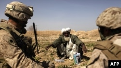 An Afghan farmer chats with a U.S. Marine officer near Marjah.
