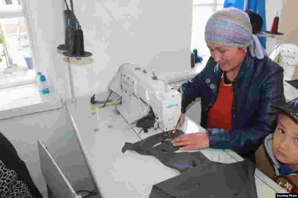 В селе Чаеке Джумгальского района ОО «Даанышман Жумгал кабары» с 1 июня 2015 года при поддержке Министерства социального развития реализует проект «Социальное швейное предприятие для трудоустройства людей с ограниченными возможностями здоровья». На этом предприятии более 10 ЛОВЗ получают дополнительный заработок. На фото - бенефициар-швея Асанбекова Назгуль. Из-за того, что не на кого оставить ребенка, она берет его с собой на работу. Автор: Допоев Жапарбек Карагулович, руководитель проекта.