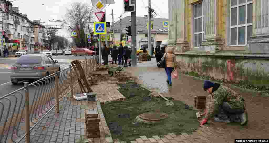 Рабочий за укладкой тротуарной плитки возле храма святых равноапостольных князя Владимира и Ольги Киевского патриархата