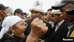A supporter of President Kurmanbek Bakiev (left) argues with interim government followers attempting to hold a rally at the central square in Jalal-Abad on April 14.