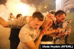 Protestatari care cară un bărbat rănit în timpul protestelor din Minsk din 9 august după scrutinul prezidențial denunțat drept viciat. Luni de proteste au urmat după alegerile în care Aleksandr Lukașenko a fost declarat câștigător, dar Vestul și opoziția nu îl recunosc drept președinte și afirmă că votul a fost fraudat. (Uladz Hrydzin, RFE/RL)