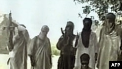Jundallah militants stand over a blindfolded and kneeling kidnapped Iranian security worker, in footage broadcast by Al-Arabiyah in June 2000.