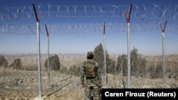 A soldier stands guard along the border fence at the Angoor Adda outpost on the border with Afghanistan in South Waziristan tribal district in western Pakistan.
