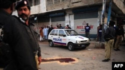 Pakistani police surround a bullet-riddled police vehicle following the attack in Karachi on April 5. A Pakistani commission says ethnic, sectarian, and politically linked violence has killed at least 300 people so far this year in Karachi.