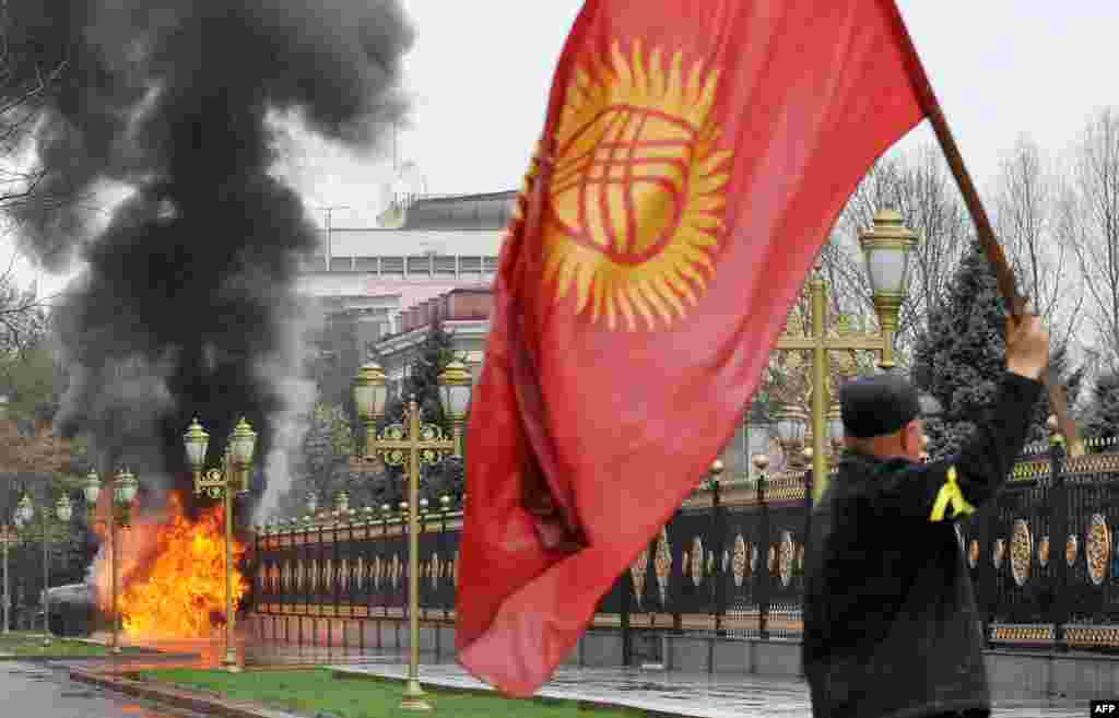 An opposition supporter waves the Kyrgyz flag near the main government building during antigovernment protests in Bishkek on April 7, 2010.