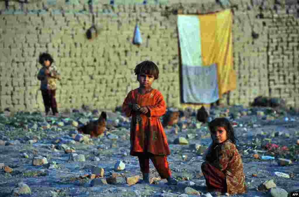 Afghan internally displaced children look on outside their temporary house on the outskirts of Jalalabad in Nangarhar Province. (AFP/Noorullah Shirzada)