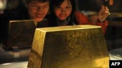 Люди смотрят на выставленный в Тайване золотой слиток весом 220 килограммов.