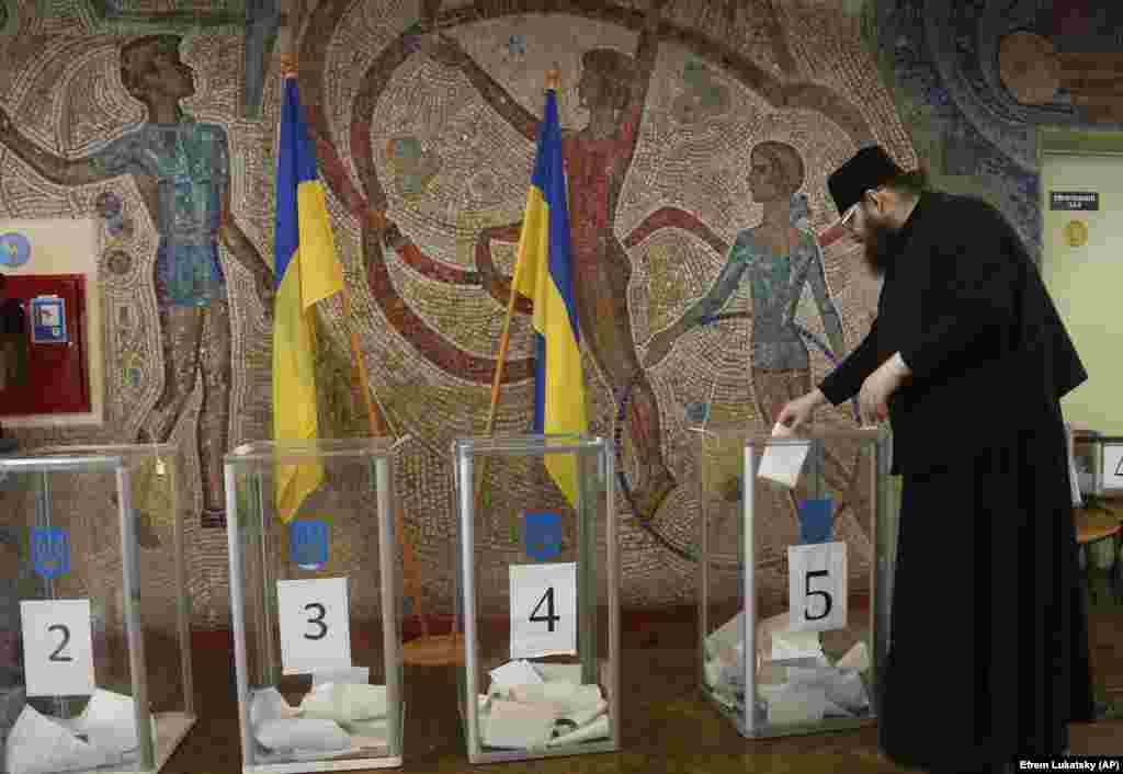 An Orthodox priest casts his ballot at a Kyiv polling station. (AP/Efrem Lukatsky)