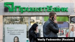 People walk past a branch of PrivatBank, the country's biggest lender, in Kyiv.