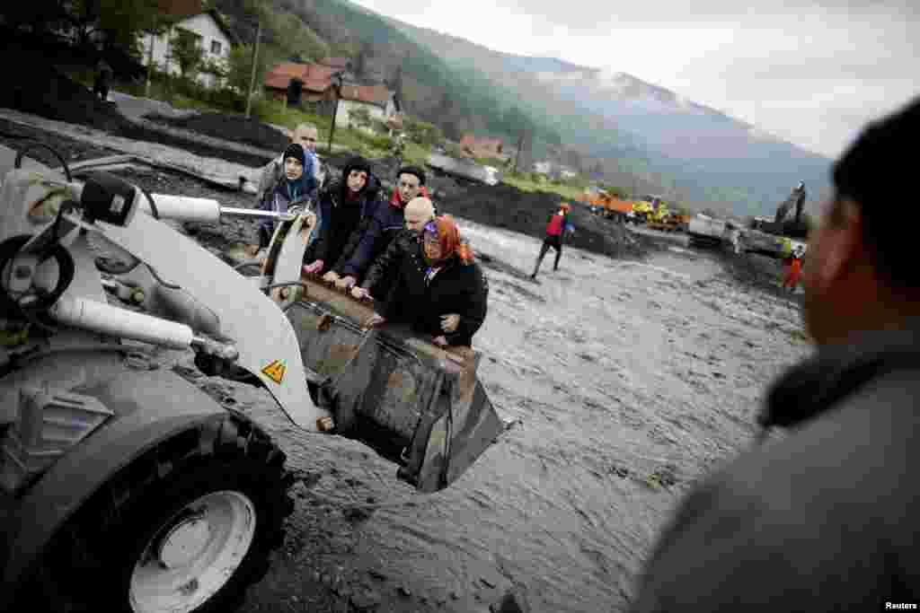 Residents of the flooded Bosnian village of Topcic Polje are evacuated from their homes by backhoe on May 16. (Reuters/Davo Rucic)