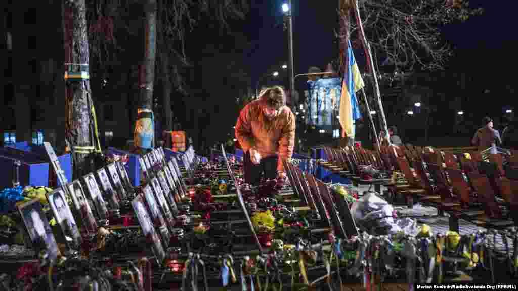 Жінка запалює свічки біляпам'ятника Героям Небесної сотні