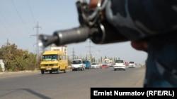 Сотрудник сил безопасности стоит на дороге в предвыборные дни в Оше.