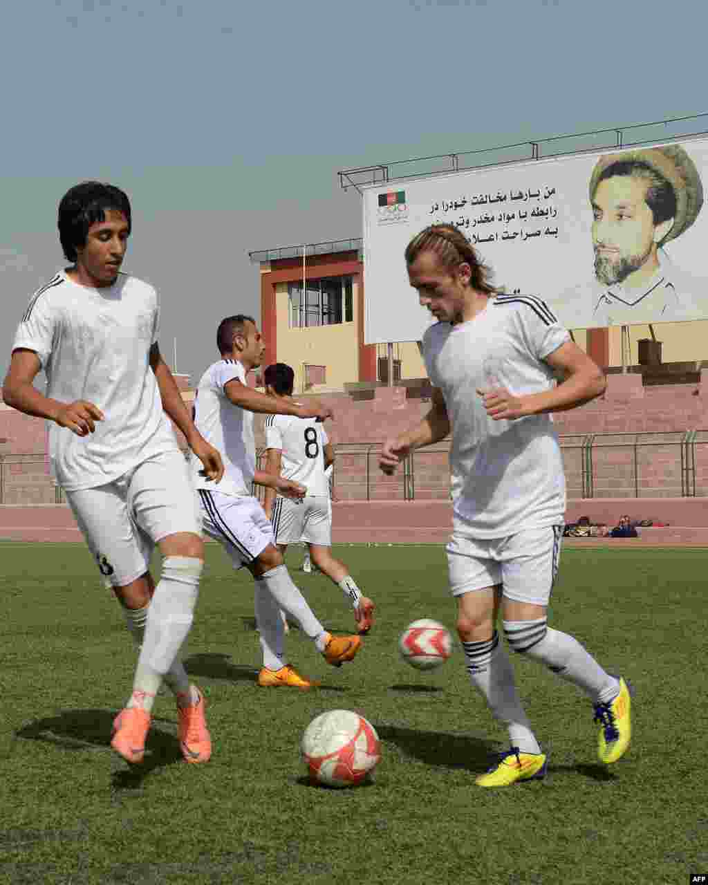 Afghan football players training in Kabul with a poster of legendary Afghan commander Ahmad Shah Masud in the background.