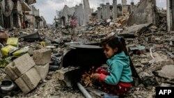 طفلة سورية بين حطام الأبنية في كوباني