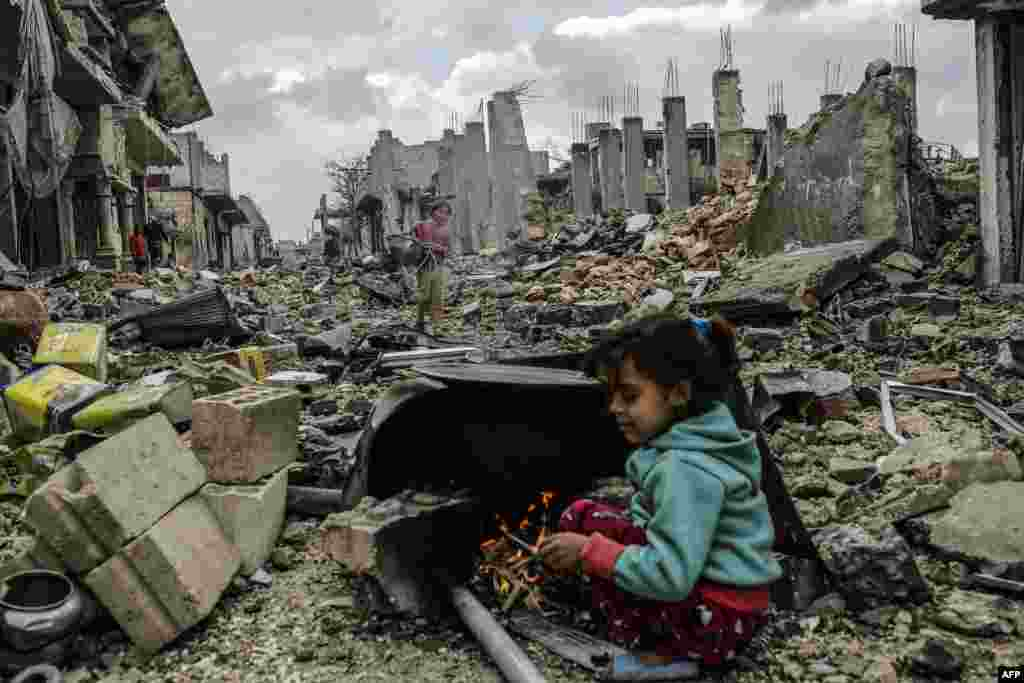 Kurdish Syrian girls are pictured among destroyed buildings in the Syrian Kurdish town of Kobani. (AFP/Yasin Akgul)