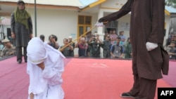 An Acehnese woman in Indonesia is caned by a religious officer for spending time in close proximity to a man who was not her husband, a crime under Shari'a law, in February.