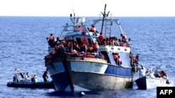 Сделанный в августе этого года снимок судна с мигрантами, которым оказывают помощь итальянские военные