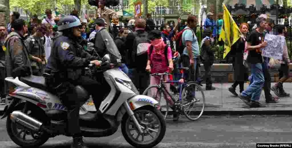 A police officer rides alongside Occupy Wall Street protesters as they march from New York City's Bryant Park to Union Square.