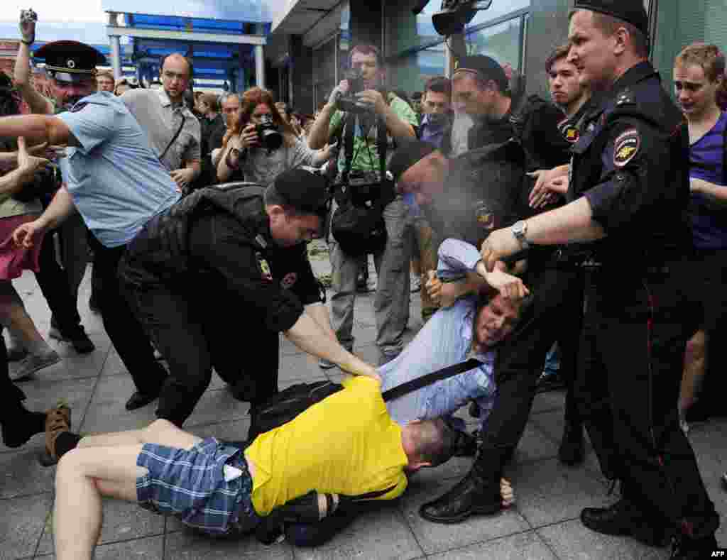 Police officers separate an Orthodox activist and gay-rights activist outside the State Duma.