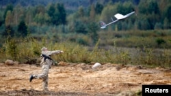 Беларус аскари Минск жанубидаги Осипович шаҳри яқинида дрон учираётган пайт, 2013 йил 25 сентябрь.