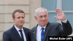 French President Emmanuel Macron, left, shake hands with Israeli Prime Minister Benjamin Netanyahu as he waves waves good-bye to the media after a meeting at the Elysee Palace in Paris, France, Sunday, July 16, 2017.