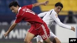 Odil Axmedov xitoylik Gao Lin bilan to'p uchun kurashmoqda, Osiyo Kubogi 2011, Qatar.