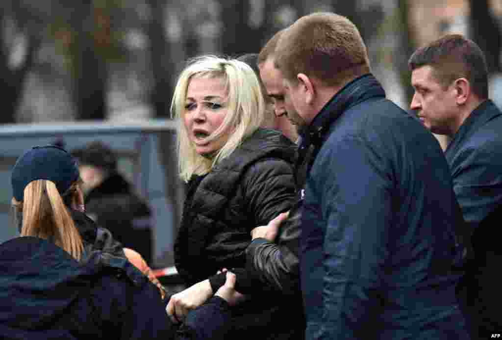 Policemen restrain Maria Maksakova, the wife of former Russian lawmaker Denis Voronenkov, as she reacts near his body in the center of Kyiv on March 23. Voronenkov was gunned down in broad daylight. The attacker was shot in the ensuing gunbattle with Voronenkov's lone bodyguard and apprehended by police on the street nearby. He later died in hospital, officials said, but there was initially no word of his identity. (AFP/Sergei Supinsky)
