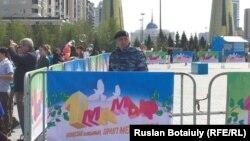Сотрудник сил безопасности стоит за оцеплением в день празднования Дня единства народа Казахстана. Астана, 1 мая 2016 года.