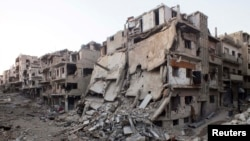 Разрушенные здания на улицах осажденного сирийского города Хомса, 12 июля 2013 года.