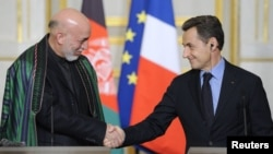 French President Nicolas Sarkozy (right) and Afghan President Hamid Karzai shake hands at a news conference after talks and a treaty signing at the Elysee Palace in Paris on January 27.